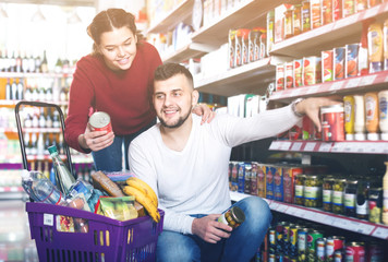 satisfied couple choosing purchasing canned food for week at supermarket