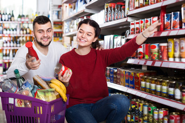 active couple choosing purchasing canned food for week at supermarket