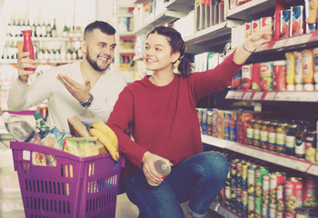 Smiling young couple purchasing at grocery store
