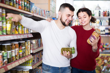 Happy family choosing purchasing canned food for week at supermarket