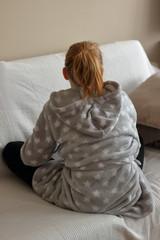 Obraz Młoda blondynka siedzi po turecku, samotnie na sofie, wpatruje się w ścianę, ubrana jest  w szary szlafrok i ciemne getry, odwrócona tyłem, sofa ma jasną narzutę, jasna ściana w tle - fototapety do salonu