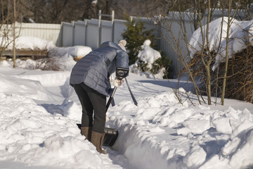 A woman cleans a shovel of snow on a site in a country house after a snowstorm.