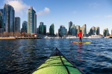 Wall Mural - Kayaking and Paddle Boarding in Coal Harbour during a vibrant sunny morning. Taken in Downtown Vancouver, British Columbia, Canada.