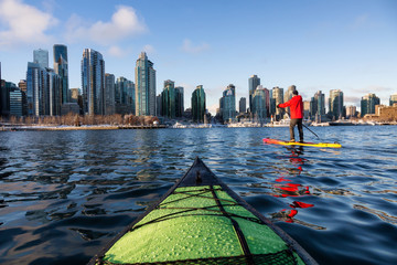 Kayaking and Paddle Boarding in Coal Harbour during a vibrant sunny morning. Taken in Downtown Vancouver, British Columbia, Canada. Fototapete