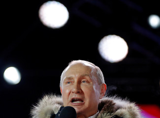 Russian President and Presidential candidate Vladimir Putin delivers a speech during a rally and concert marking the fourth anniversary of Russia's annexation of the Crimea region in Moscow