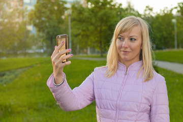 Beautiful young blonde caucasian woman taking a selfie with smartphone.