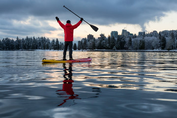 Wall Mural - Adventurous male is paddle boarding near Stanley Park with Downtown City Skyline in the background. Taken in Vancouver, BC, Canada, during a vibrant winter sunrise.