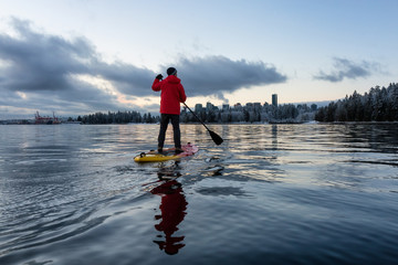 Fotomurales - Adventurous male is paddle boarding near Stanley Park with Downtown City Skyline in the background. Taken in Vancouver, BC, Canada, during a vibrant winter sunrise.