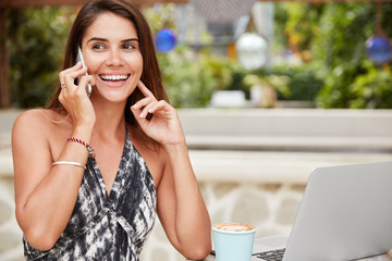 Smiling relaxed female freelancer being satisfied with online business, checks bank account via smart phone, learn some information in internet on laptop computer, drinks latte or hot coffee
