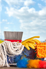 Pile of equipment for cleaning. Cleaning service basket with cleaning products on window sky background. Household chore concept.