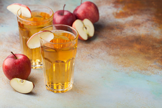 Two glasses of red Apple juice with mint and ice on an old rusty table. Soft drink on a blue background. With copy space