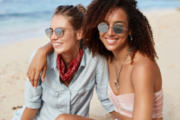 Adorable woman with Afro hairstyle embraces her female partner, beinng lesbains, enjoy togetherness and calm atmospere at seaside, admire views, have happy looks. People, lifestyle, recreation