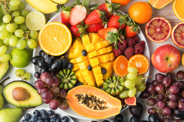 Healthy food background, assortment of fruits in rainbow colours on the off white table, top view, selective focus