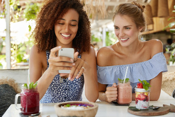 Gay couple have romantic date together at cozy cafe, enjoy online communication on modern smart phone and fresh cocktails. Positive African American woman surfes internet or webpages via cellular