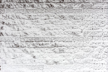 Brick wall covered with snow. Iced winter surface texture.  Copyspace for product placement or text