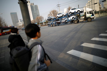 Children look at a truck transporting newly manufactured GM vehicles outside its Bupyeong plant in Incheon