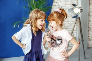 Two happy little children sing a song in karaoke. The concept is childhood, lifestyle, music, singing, friendship.