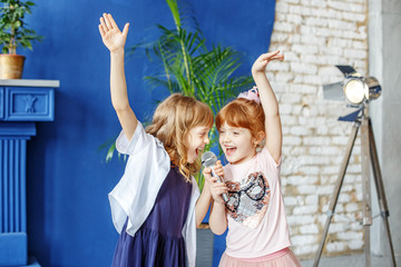 Two little funny children dance and sing a song in karaoke. The concept is childhood, lifestyle, music, singing, friendship.