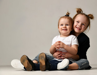 Beautiful little sisters girls kids sitting together hugging happy smiling on gray