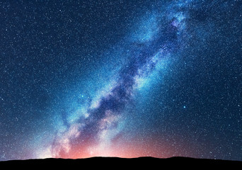 Milky Way. Space. Scenic night landscape with bright milky way, sky full of stars, orange light and hills. Shiny stars. Beautiful scene with universe. Space background with starry sky. Concept. Nature