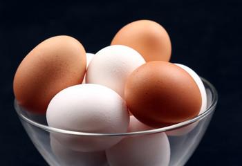 chicken eggs lie in plate on dark background.