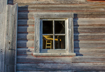wall of an old wooden farmhouse with a window
