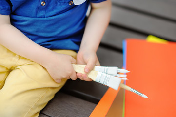 Cute little boy drawing with colorful paints in summer park