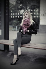 Girl is sitting at a public transport stop