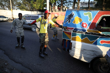 Skaters hold on to the back of a tap-tap, a collective transportation vehicle, to go along a street in Port-au-Prince