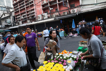 Women buy flowers at a street market in Bangkok