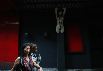 Women walk past in front of a nightclub in Bangkok