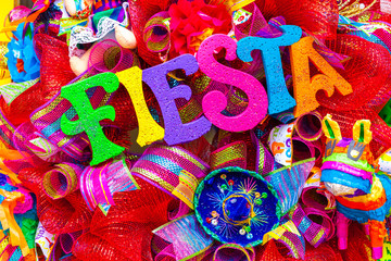 The word 'fiesta' written in colorful foam letters on multicolored mash decorated with glitter and small sombrero