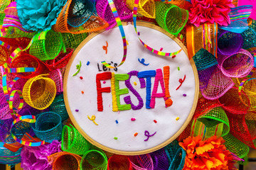 The word 'fiesta' stitched in colorful letters on multicolored mash decorated with glitter and paper flowers