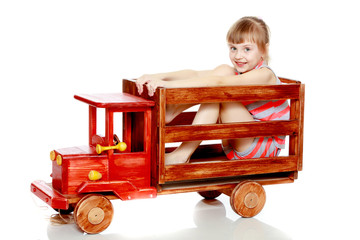 The girl is sitting on a large toy wooden car.