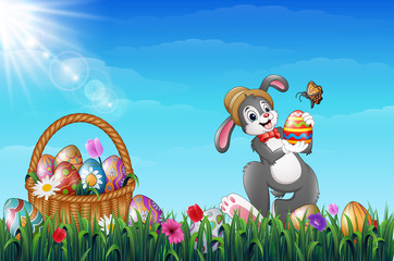 Easter bunny holding Easter eggs with a butterfly. Easter Wicker basket full of decorated Easter eggs in a grass field