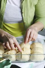 Ready to bake homemade Easter traditional hot cross buns. Female hands make a cross.