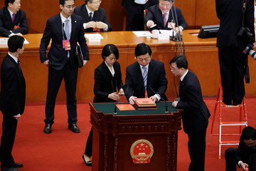 Staff members prepare for an oath-taking session at the seventh plenary session of the National People's Congress (NPC)