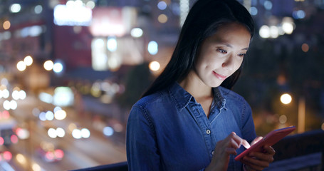 Woman use of smart phone over traffic background at night