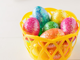 Yellow basket with colorful eggs on a white rustic table.