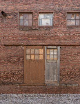 old sliding barn doors on outside brick wall of old factory