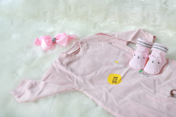 bodysuits for newborn babies with socks on white fur background.