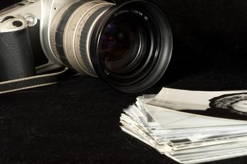 Eine alte, analoge Kamera und schwarz weiss Fotos