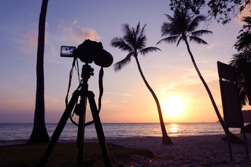 Dslr camera on a tripod while recording pictures of sunrise on the coconut beach