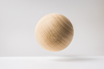 Design concept - abstract real wooden sphere with surreal layout on white surface background and it's not 3D render