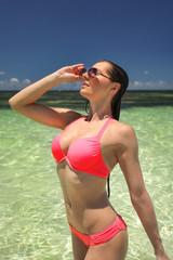 Young woman in pink bikini standing in shallow crystal clear water, her hair wet, fixing her sunglasses. Watamu, Kenya