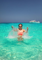 Sunglasses wearing young woman in crystal clear sea water splashing water in front of her with smiling happy face  expression. Similan Islands, Thailand