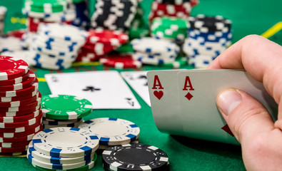 Close up of a poker player holding playing cards .