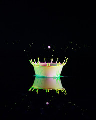 Tiny Drops Of Acrylic Paint Are Placed On A Shiny Black Surface And A Water Drop Is Released From Above To Create A Crown
