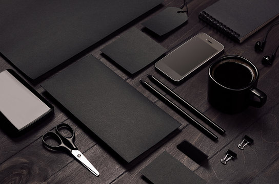Blank black corporate stationery with phone on dark stylish wood background, inclined, closeup. Branding mock up for branding, graphic designers presentations and business portfolios.