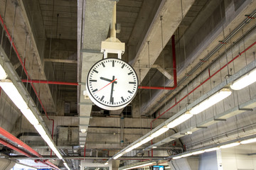 clock is hanging on the steel arch roof structure at train station,